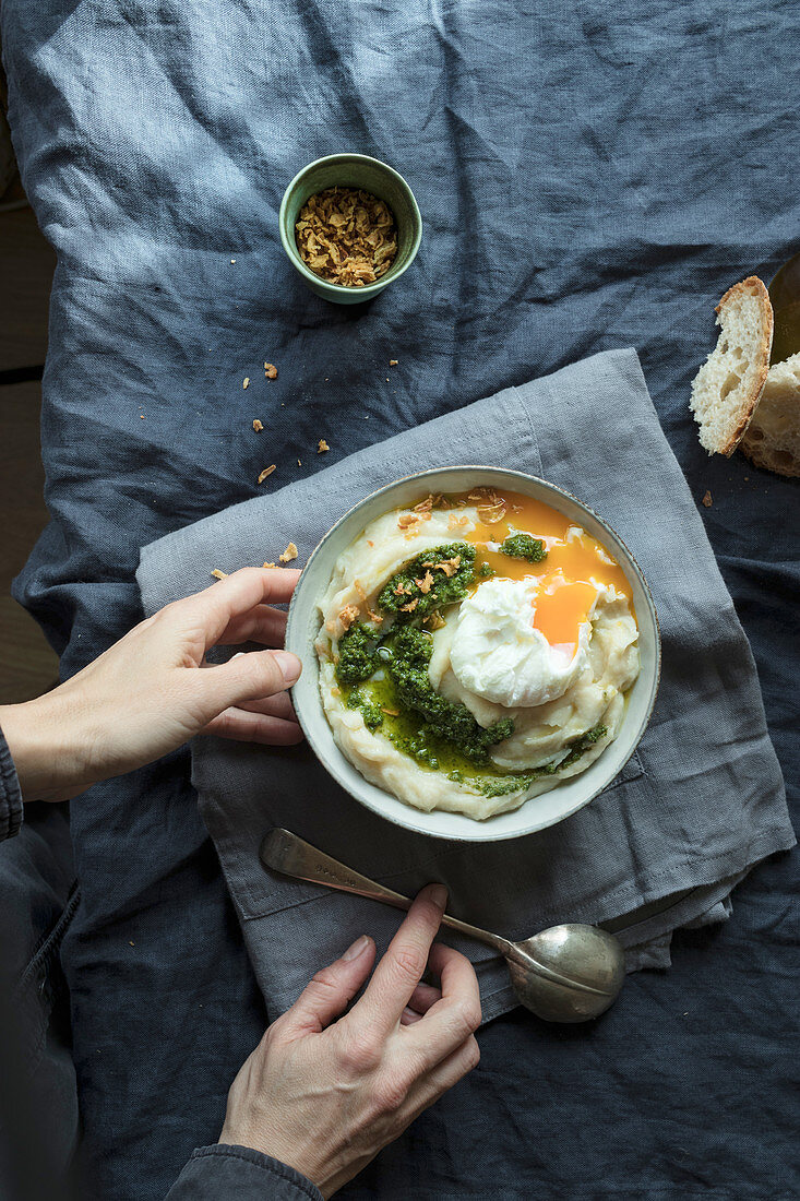 Hands holding bowl with cauliflower puree with pesto and eggs