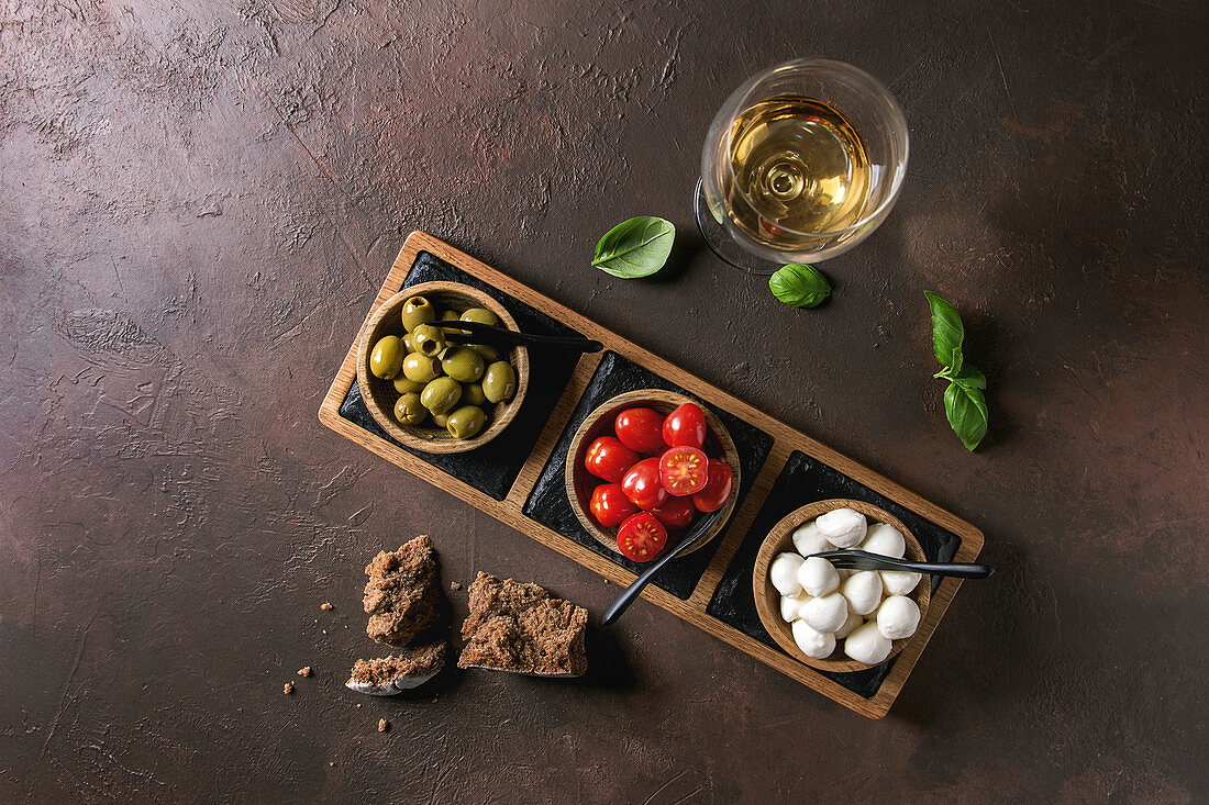 Mozzarella, cherry tomatoes, olives antipasto appetizers served in wooden bow
