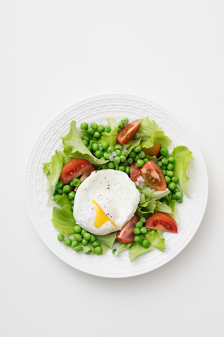 Pea salad with lettuce, tomatoes and a poached egg