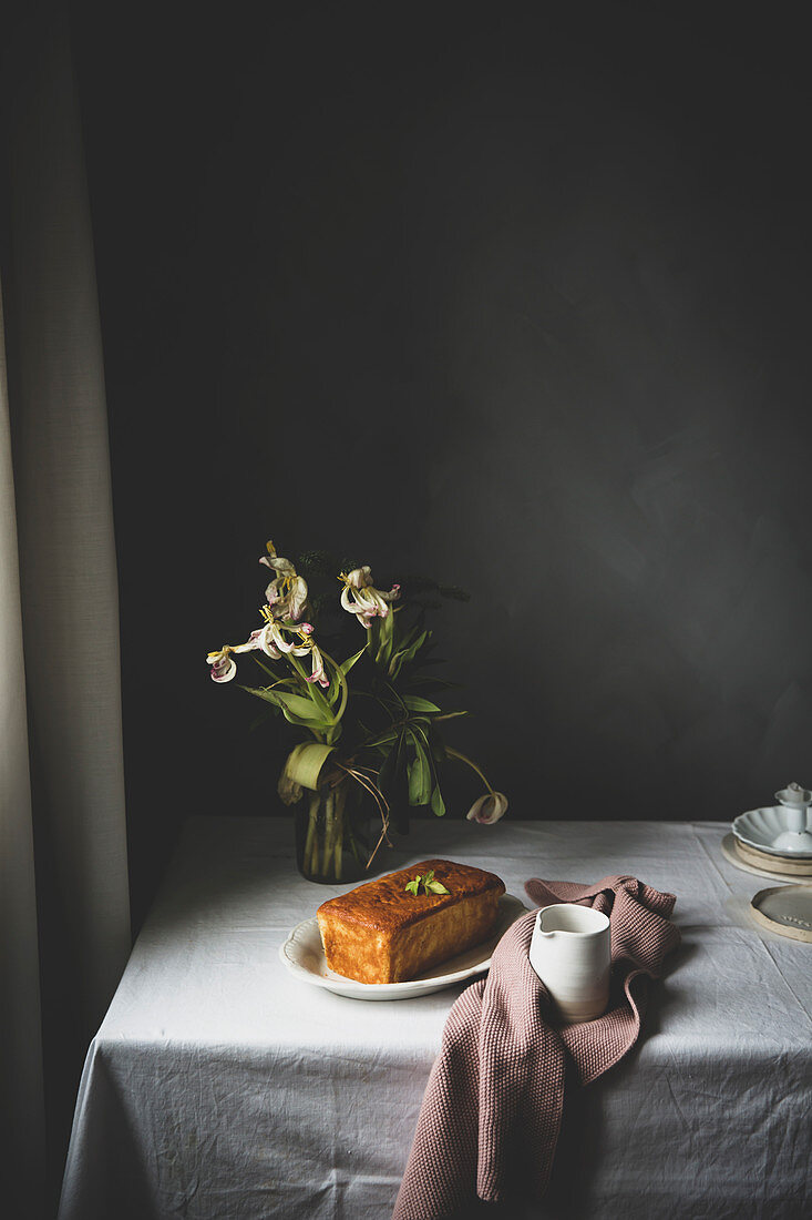 Lemon cake and pitcher served on rustic table with flowers
