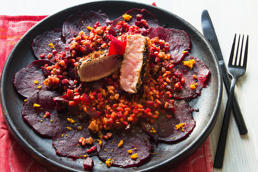 Low-carb tuna fish steak with sesame seeds on a beetroot carpaccio with bulgur salad