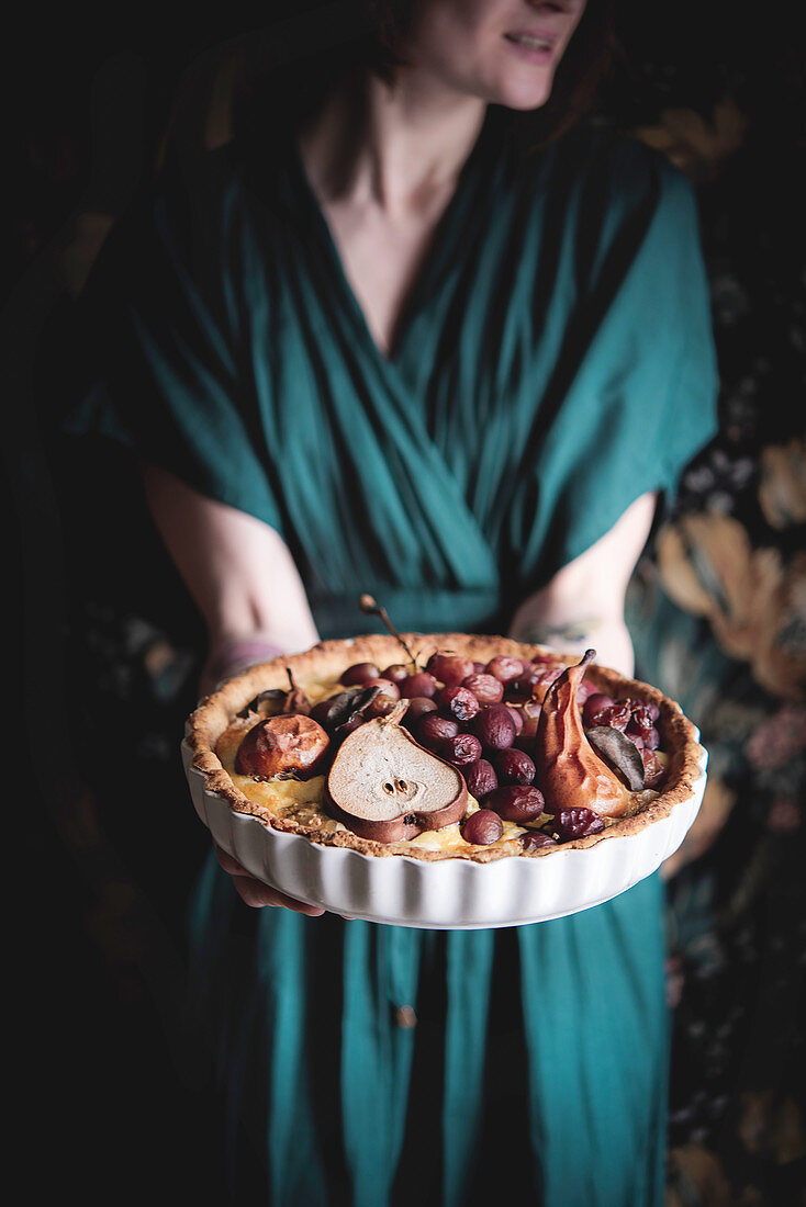 A woman serving a cheese quiche with pears and grapes