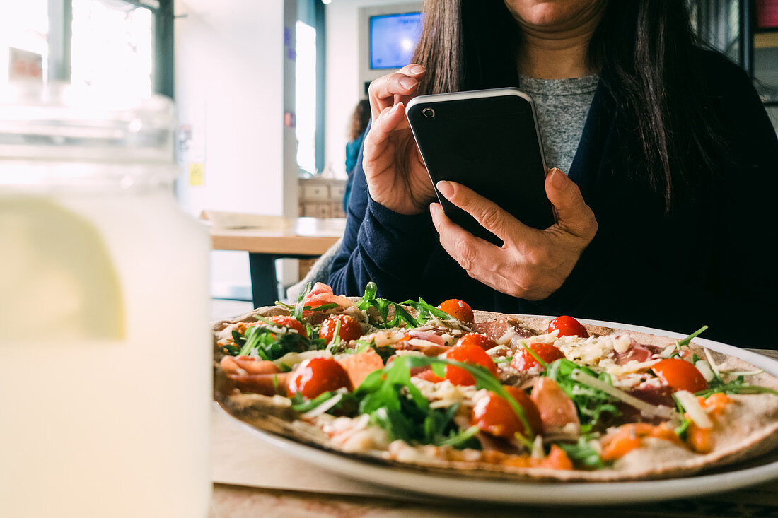 Female using mobile phone and sitting at table with delicious salad in cafe