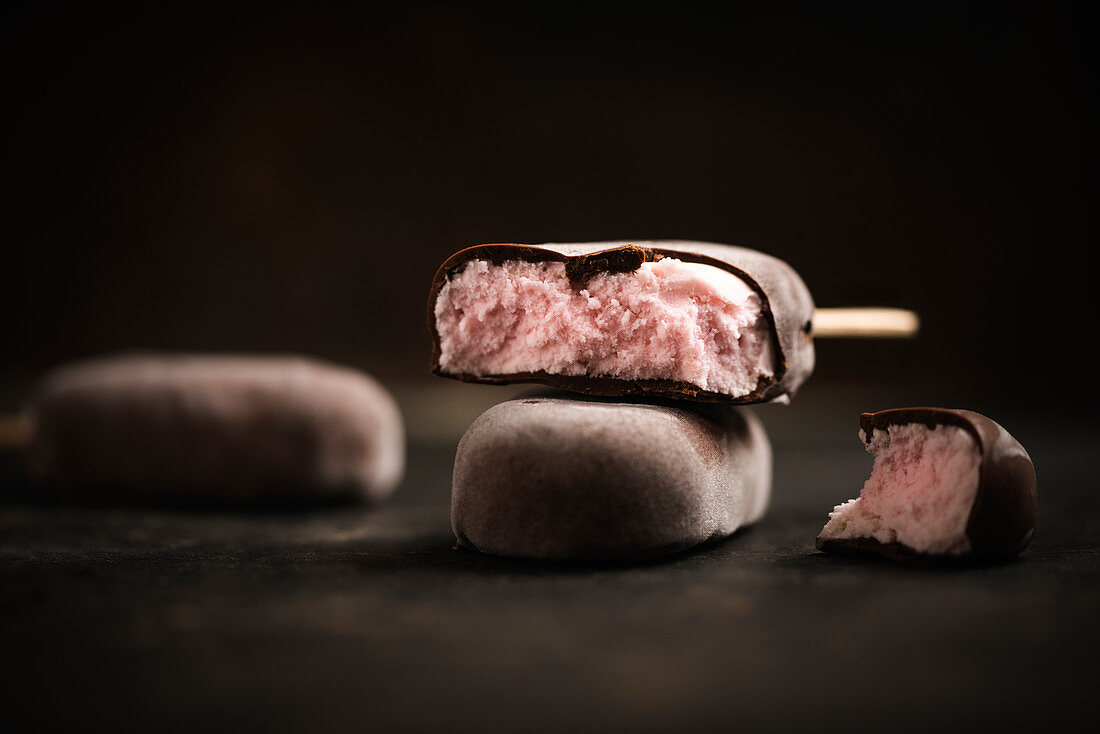 Vegan strawberry popsicles covered with dark chocolate