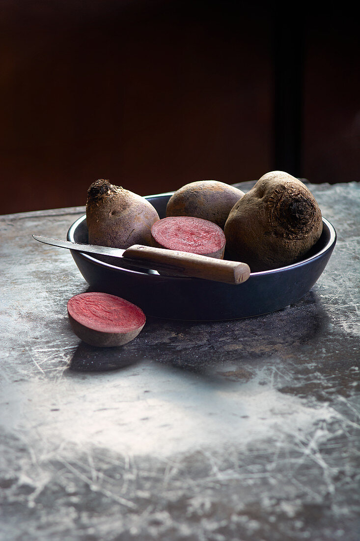 Beetroot, whole and halved, in a bowl with a knife