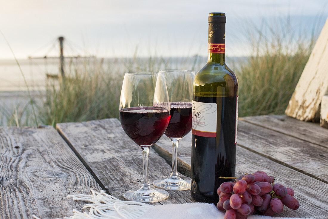 Rotwein und Trauben auf Holztisch am Strand