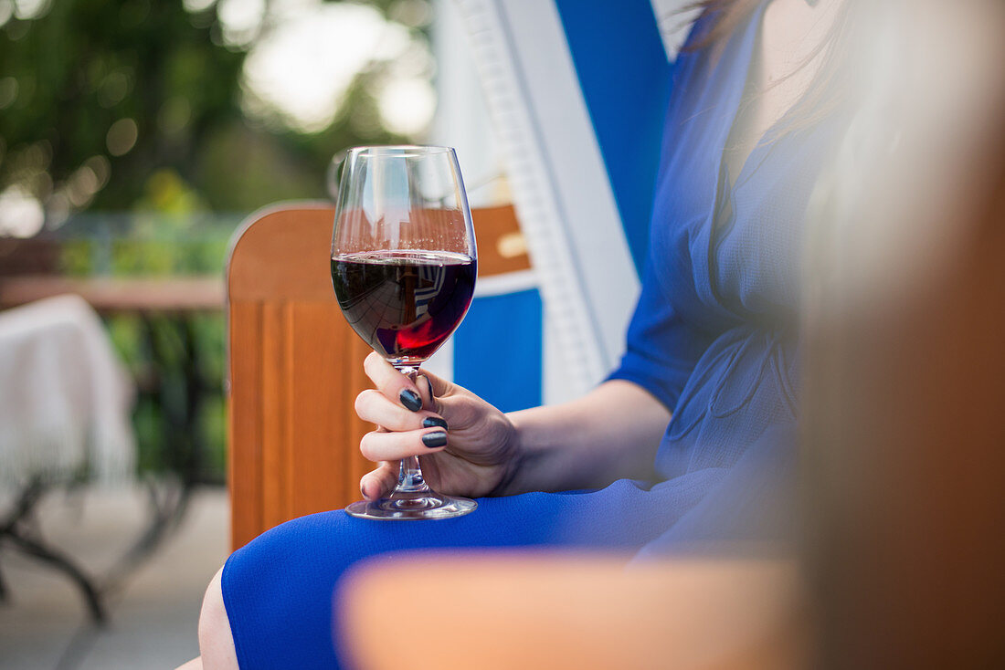 A woman sitting in a beach chair with a glass of red wine
