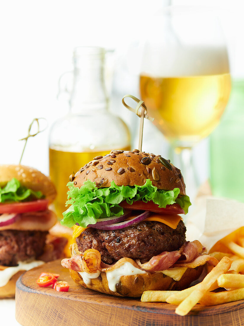 A beefburger with bacon and cheese, served with chips and beer