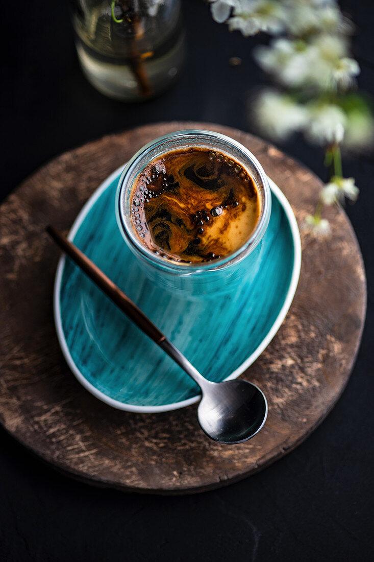 Espresso im Glas auf türkisem Unterteller mit Löffel
