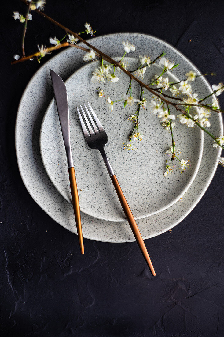 Place setting with peach blossom branch on grey plates