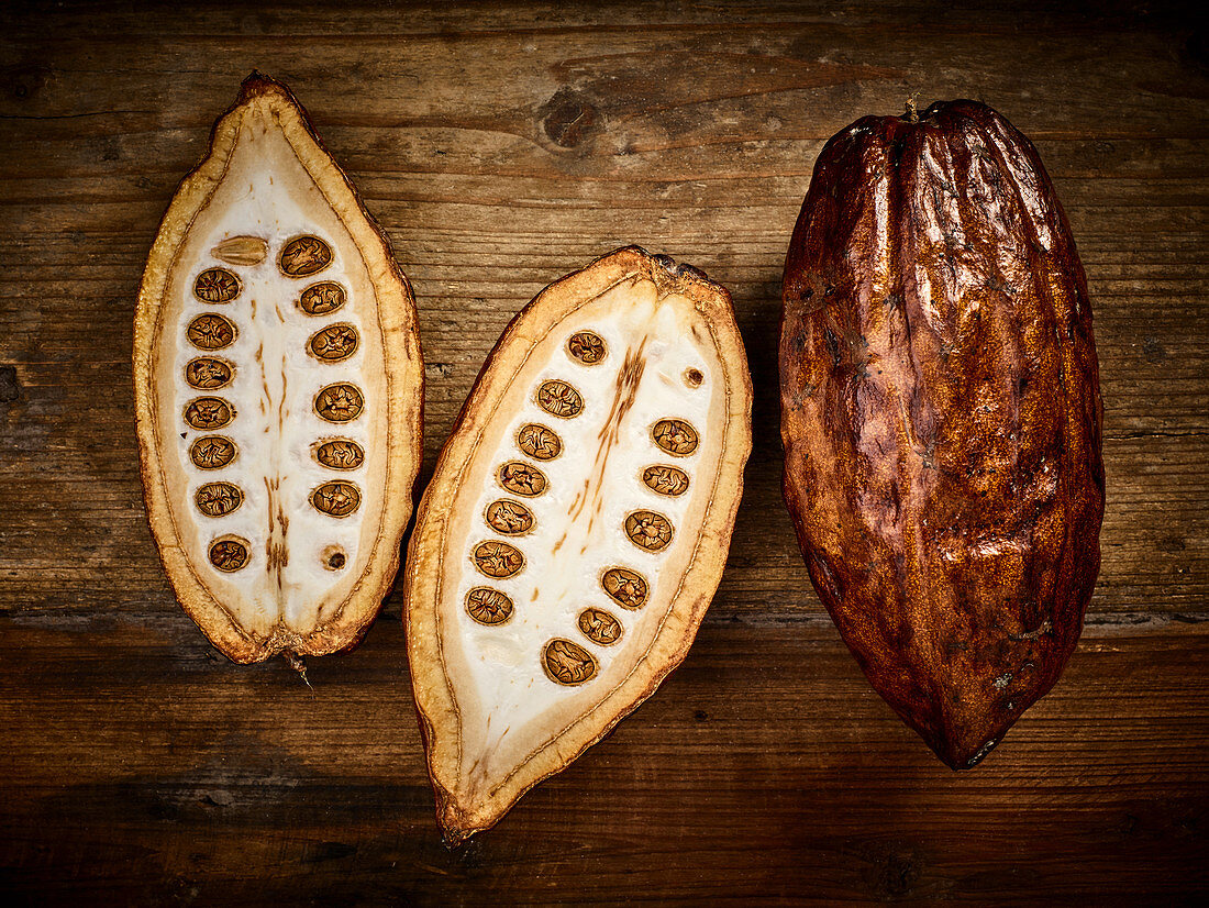 Cocoa pods, whole and halved on a wooden background