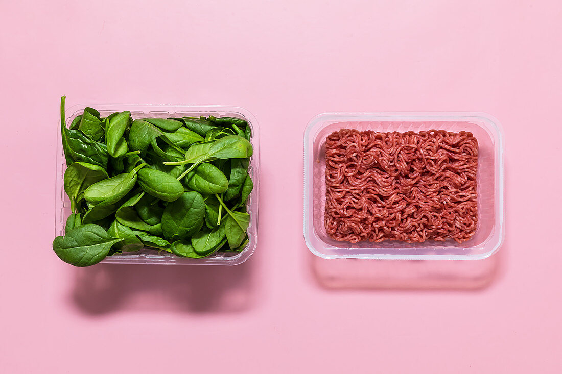 Minced meat and spinach leaves in storage containers