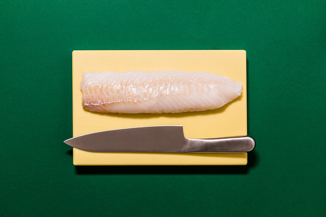 Fresh fish fillet with a knife