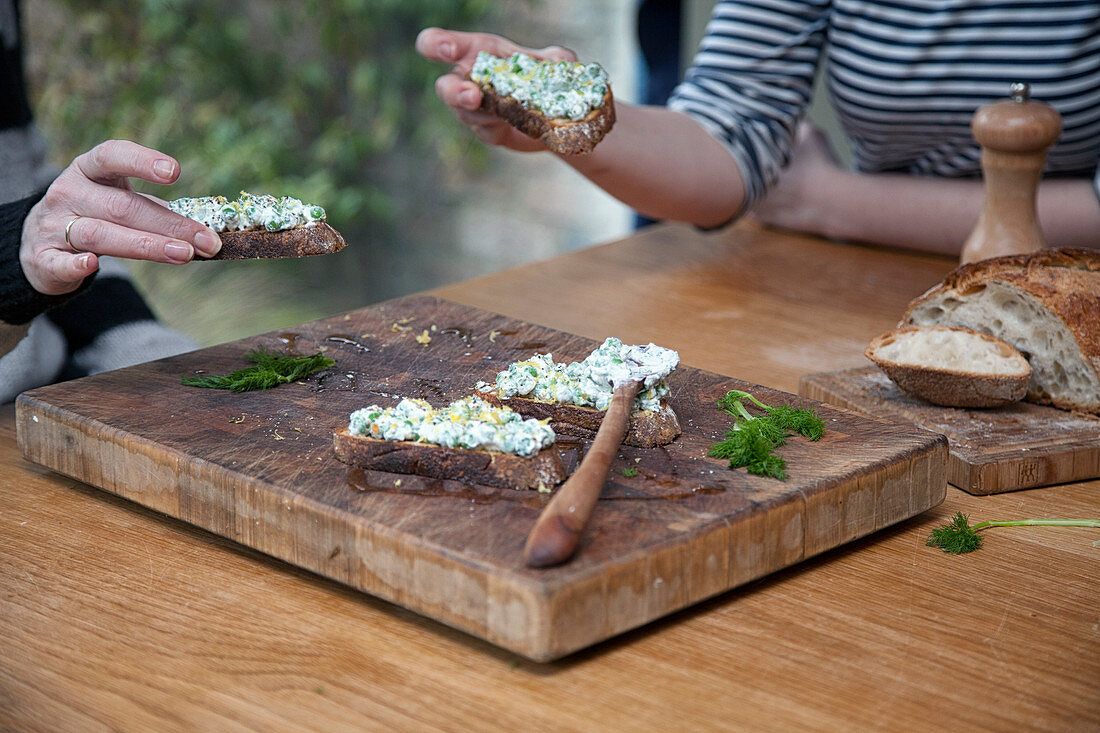 Two people eating fresh baked bread topped with Cream Cheese and peas
