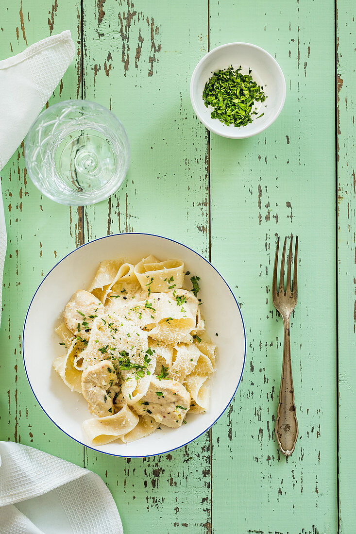 Pappardella with chicken alfredo sauce and chopped parsley