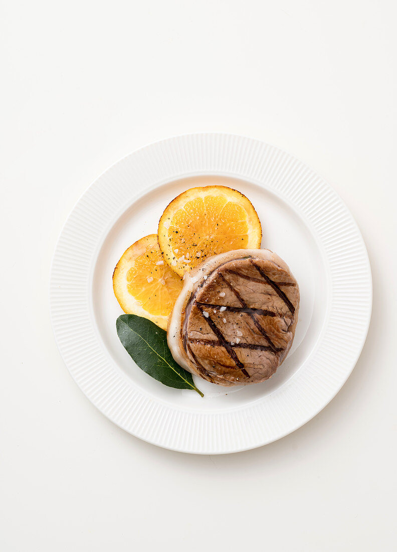 A beef medallion in a lardo coating with orange and bay leaves