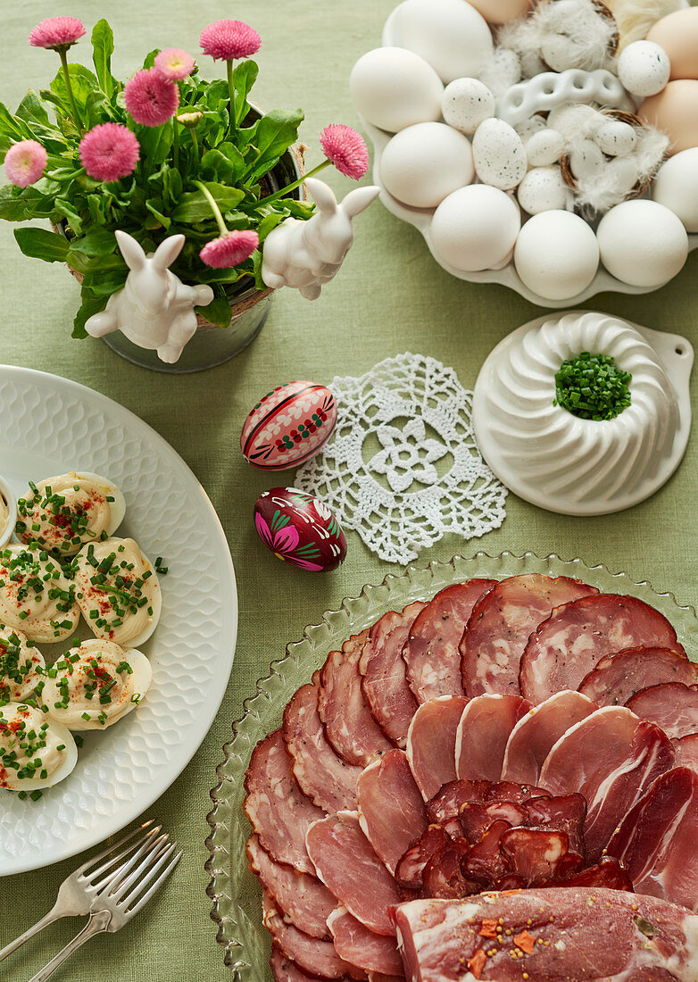 A table laid for Easter with purple Easter eggs, eggs with mayonnaise sprinkled with chives, cold cuts arranged on a glass plate