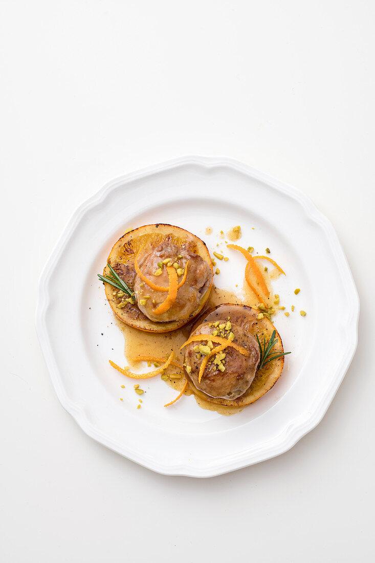 Pork medallions on orange slices with orange sauce and pistachio nuts