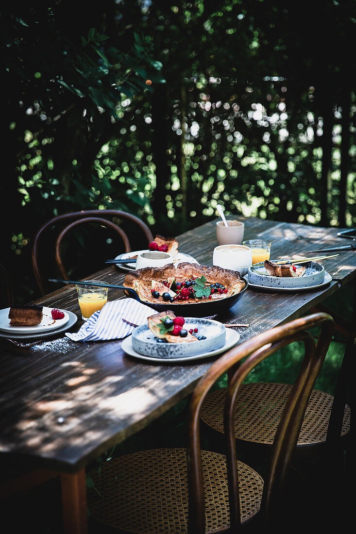 A Dutch baby omelette on a wooden table in a garden
