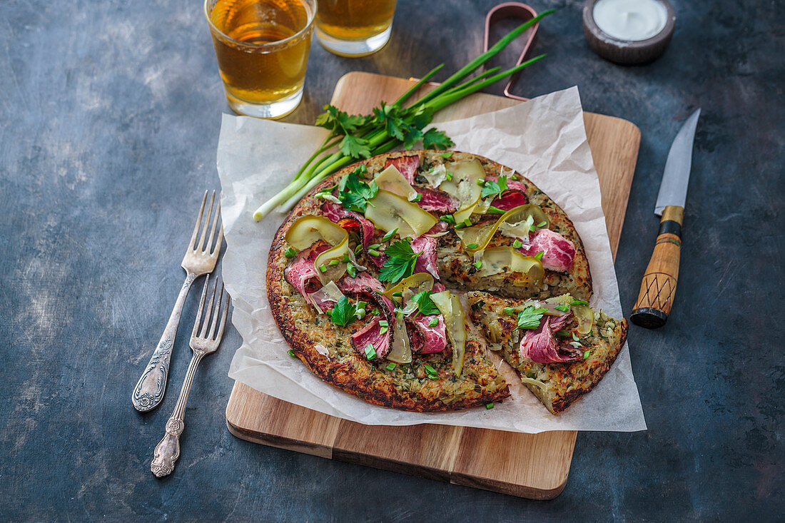 Big rosti with pastrami on a wooden cutting board
