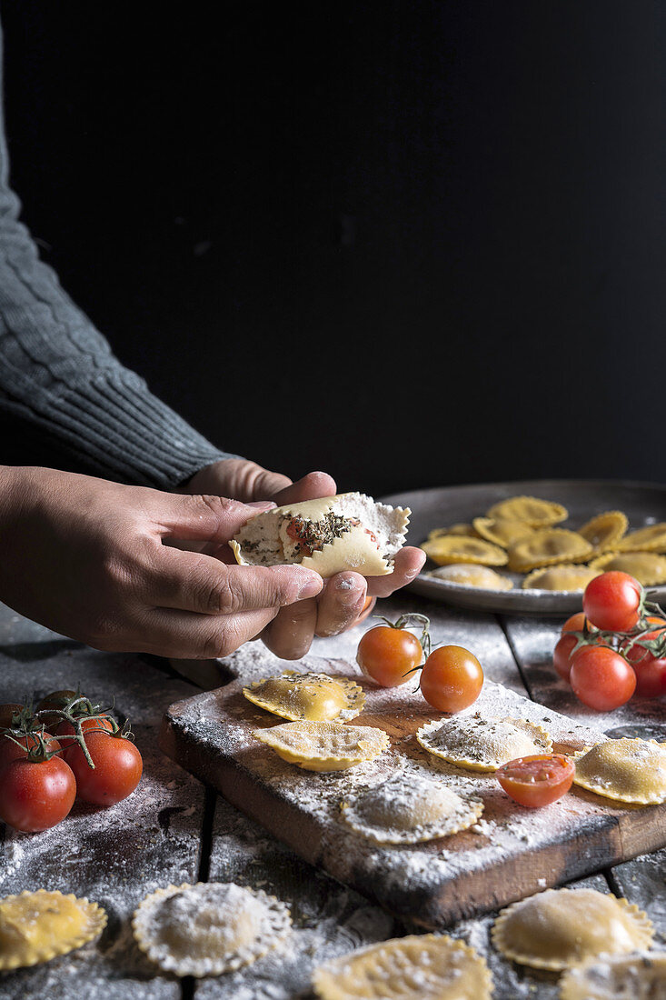 Selbstgemachte Ravioli mit Parmesan, Tomaten und Basilikum (Italien)