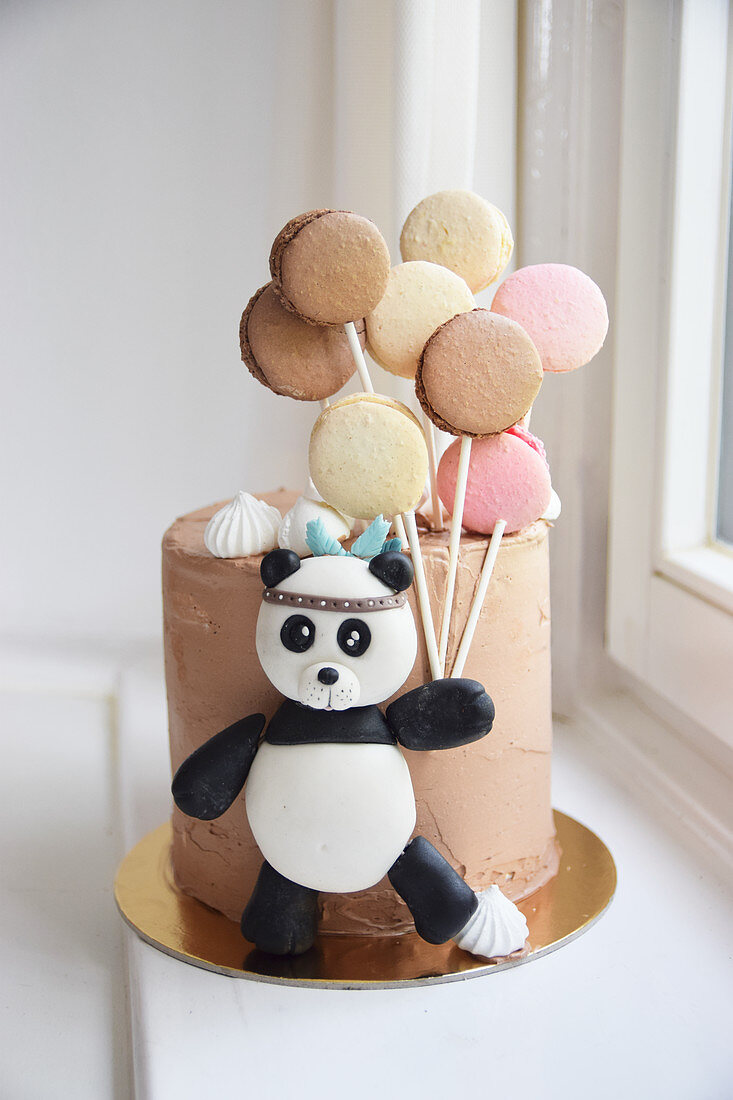 A children's birthday cake decorated with a panda and macaroons