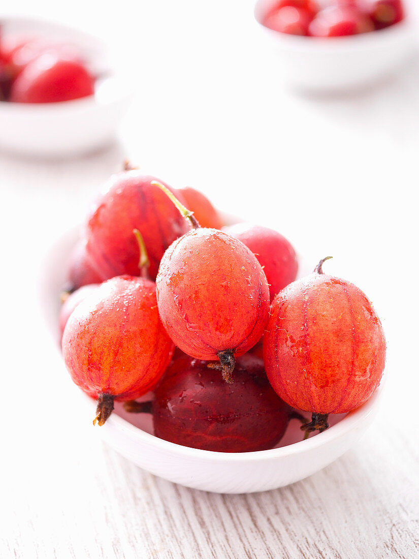 Red gooseberries in a white bowl