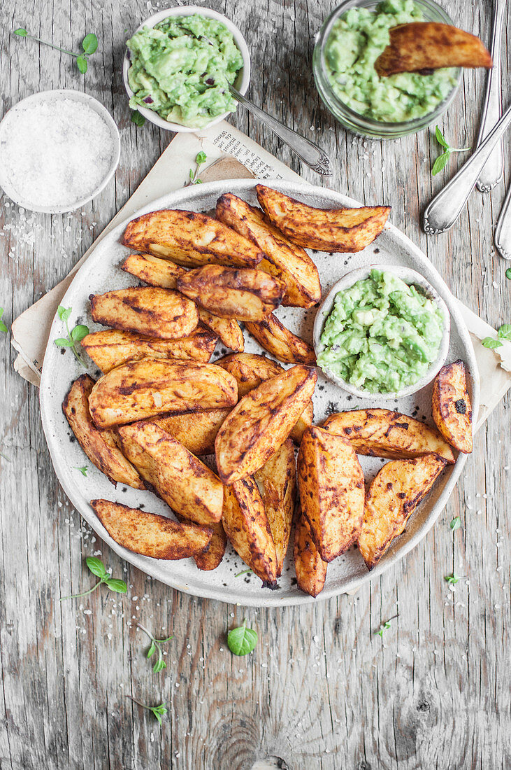 Spicy baked potatoe wedges served with guacamole