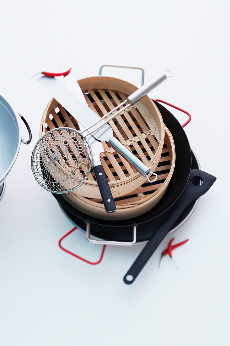 A stack of oriental cooking utensil and bamboo baskets