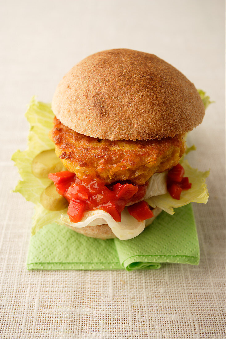 A burger with breaded camembert and sweetcorn