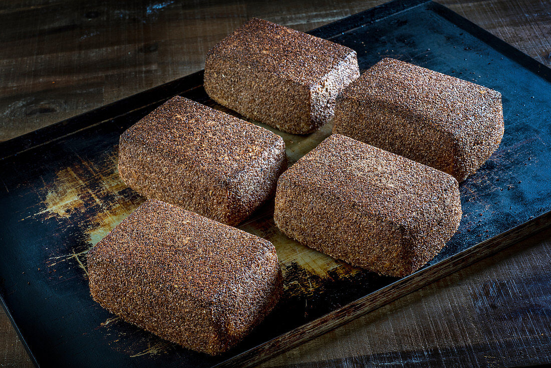 Square loaves of rye bread with flax seeds on a baking tray