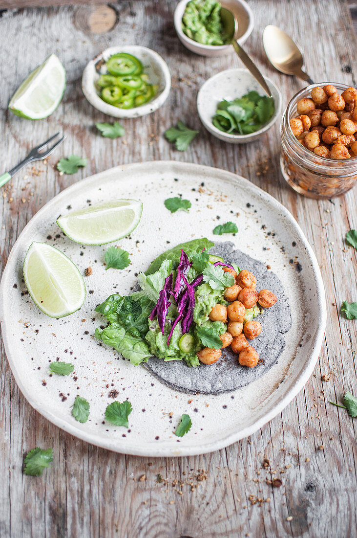 Vegan chickpeas taco with blue corn tacos, guacamole, roasted spicy chickpeas, red cabbage, cilantro, jalapeno