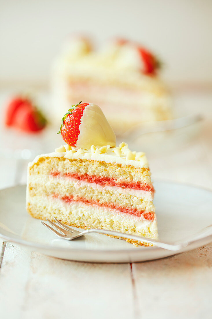 A slice of strawberry and cream cheese cake with Belgian white chocolate