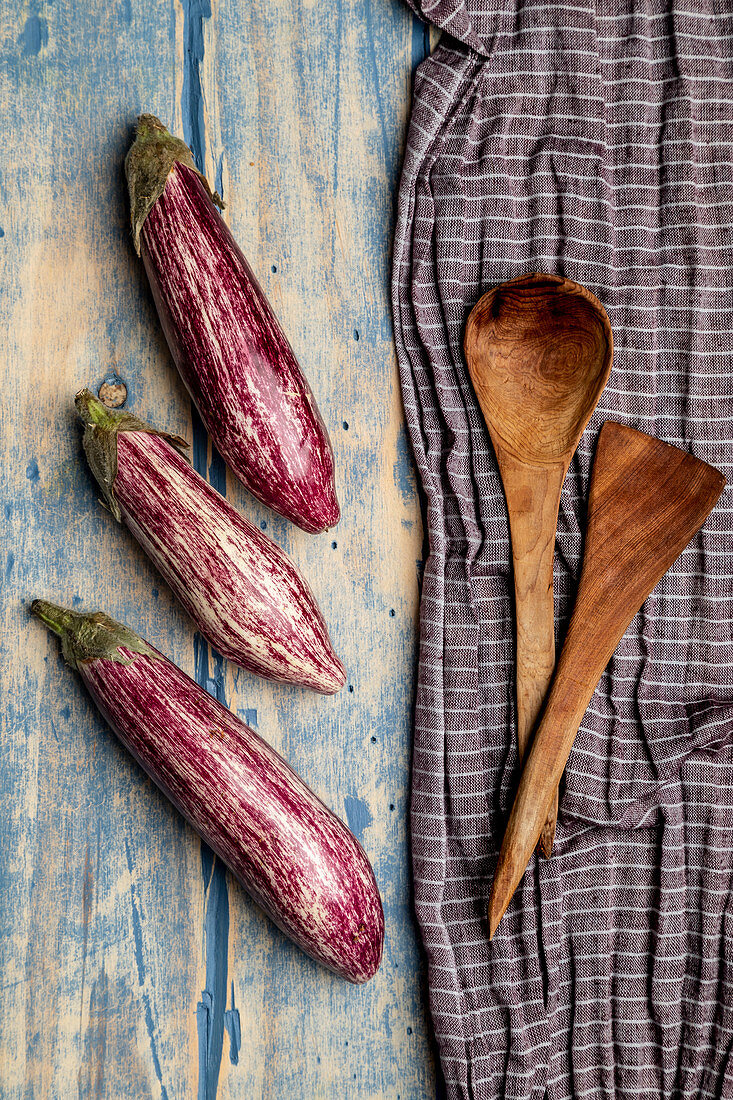Set of fresh ripe eggplants placed near piece of striped cloth on weathered wooden tabletop