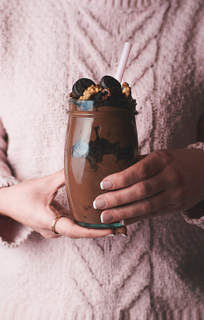 Woman in pink sweater holding glass of chocolate smoothie with nuts and candies
