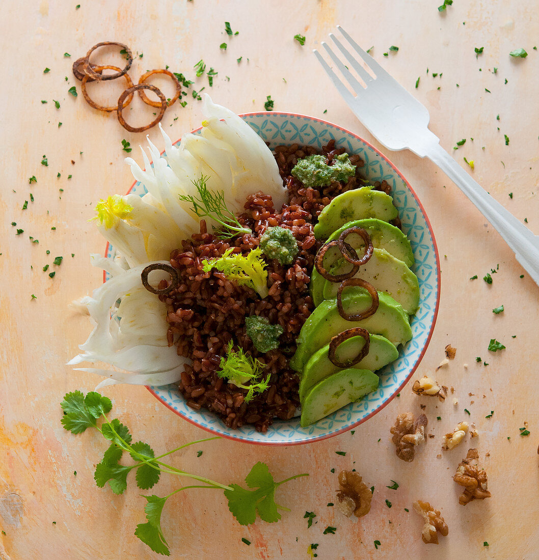 Red rice bowl with fennel, avocado, fried onions and coriander pesto