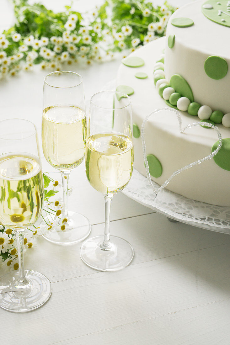 Butter cream cake with fondant for a birthday, with chamomile flowers and champagne glasses