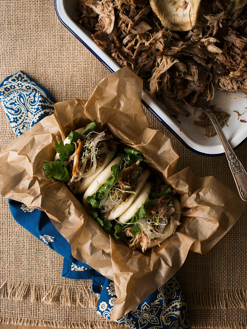 Metal bowl with delicious pulled pork and fresh bao bun placed on ornamental and linen napkins