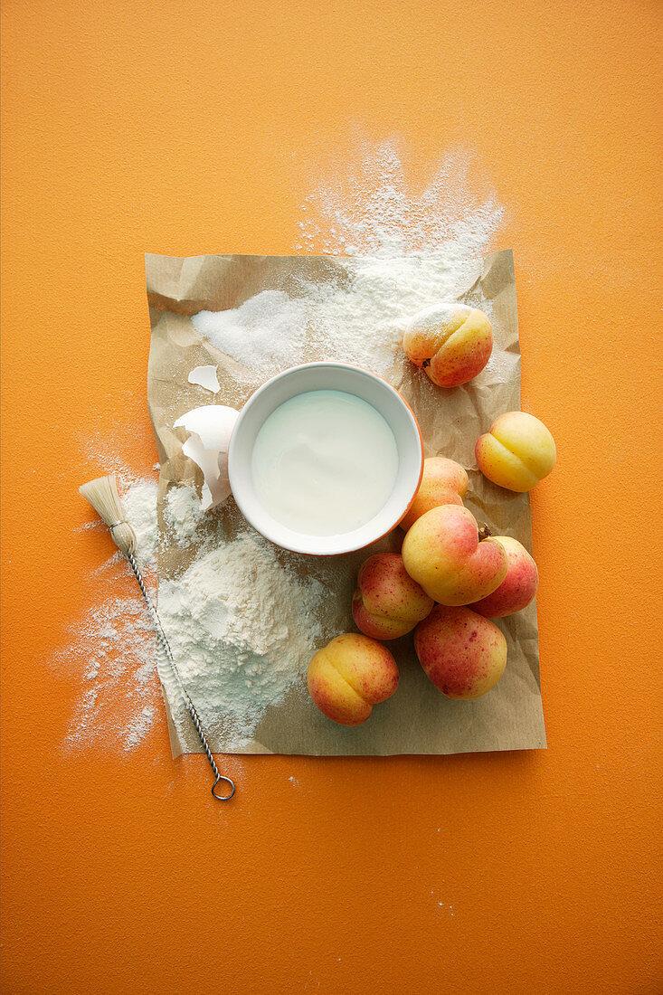 Ingredients for a peach dessert: flour, cream, eggs and peaches