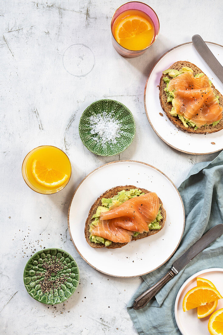 Slices of bread topped with avocado and smoked salmon for breakfast