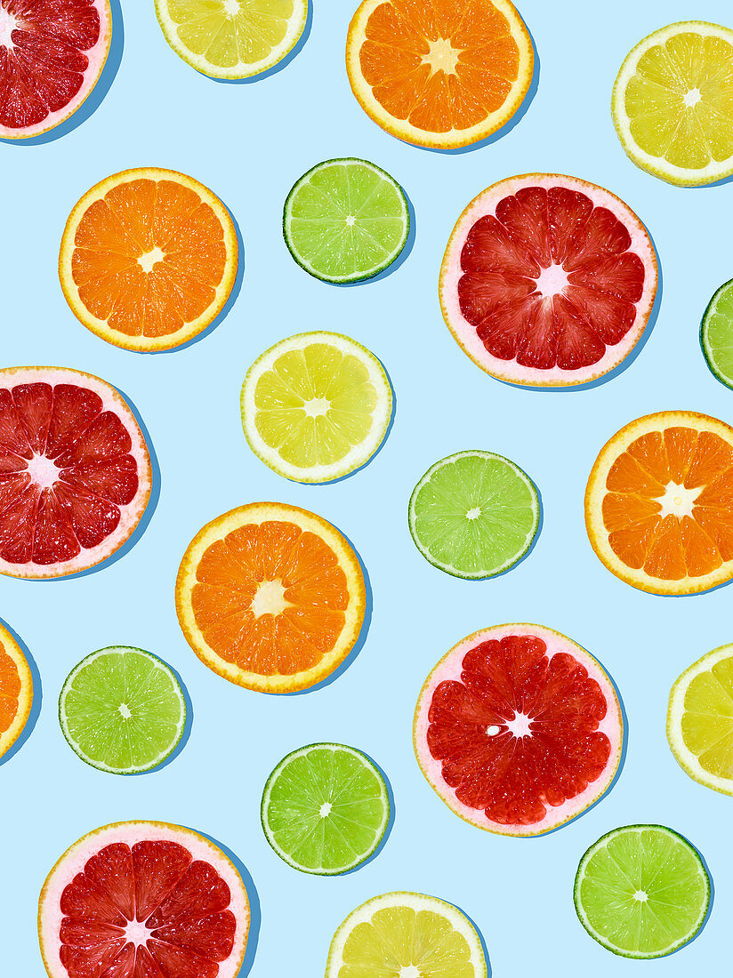 Slices of citrus fruit on a light blue surface