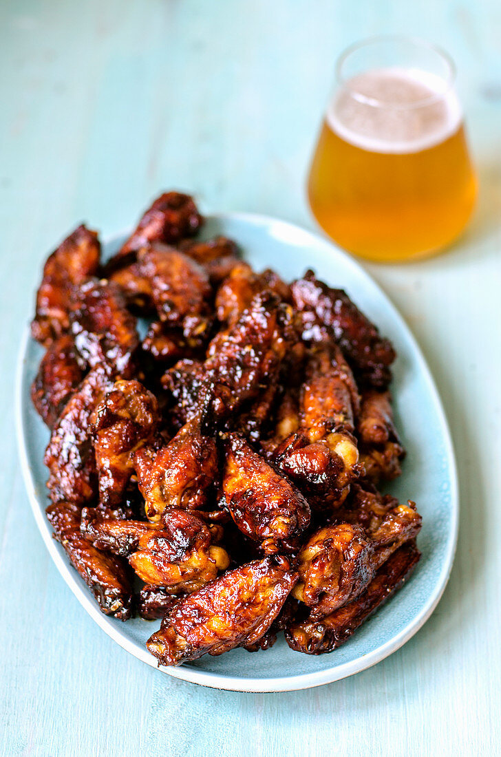 BBQ wings, pre-cut into pieces on a blue plate and fresh craft beer