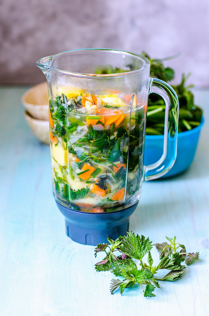 Cooked vegetables in a bowl of blender for puree soup with nettles on a blue table