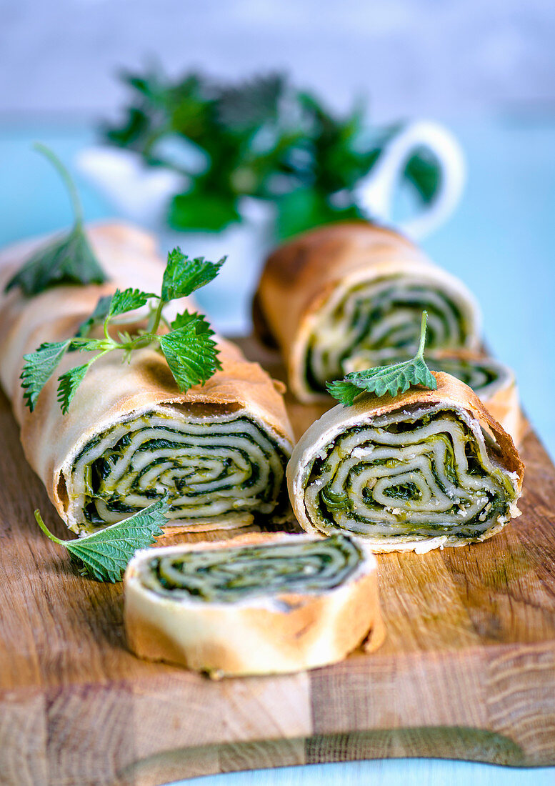 Young nettle strudel, cut into portions on a wooden board, decorated with fresh nettle leaves