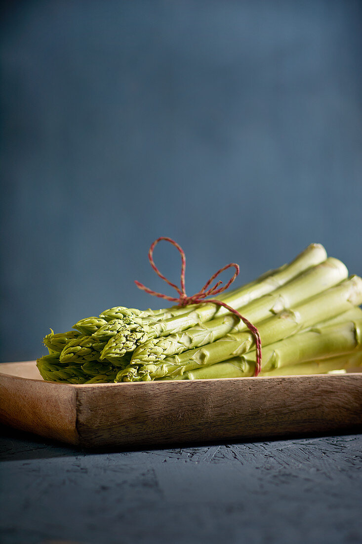 A bundle of green asparagus on a wooden dish
