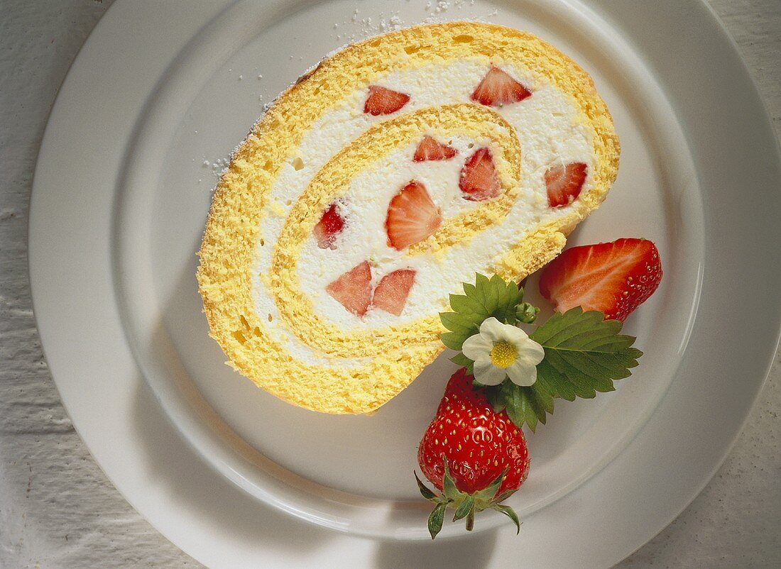A piece of strawberry roulade on a cake plate
