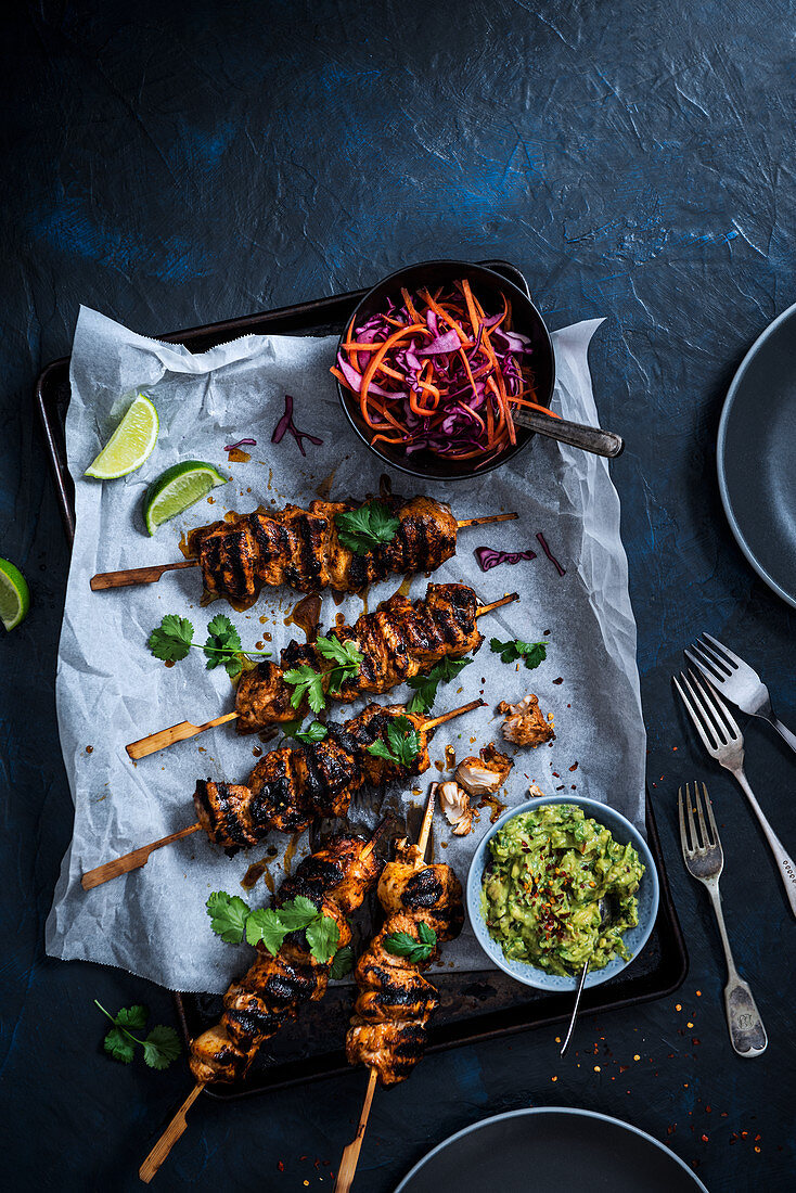 Chicken skewers marinated in garlic, smoked paprika and olive oil with guacamole and cabbage slaw
