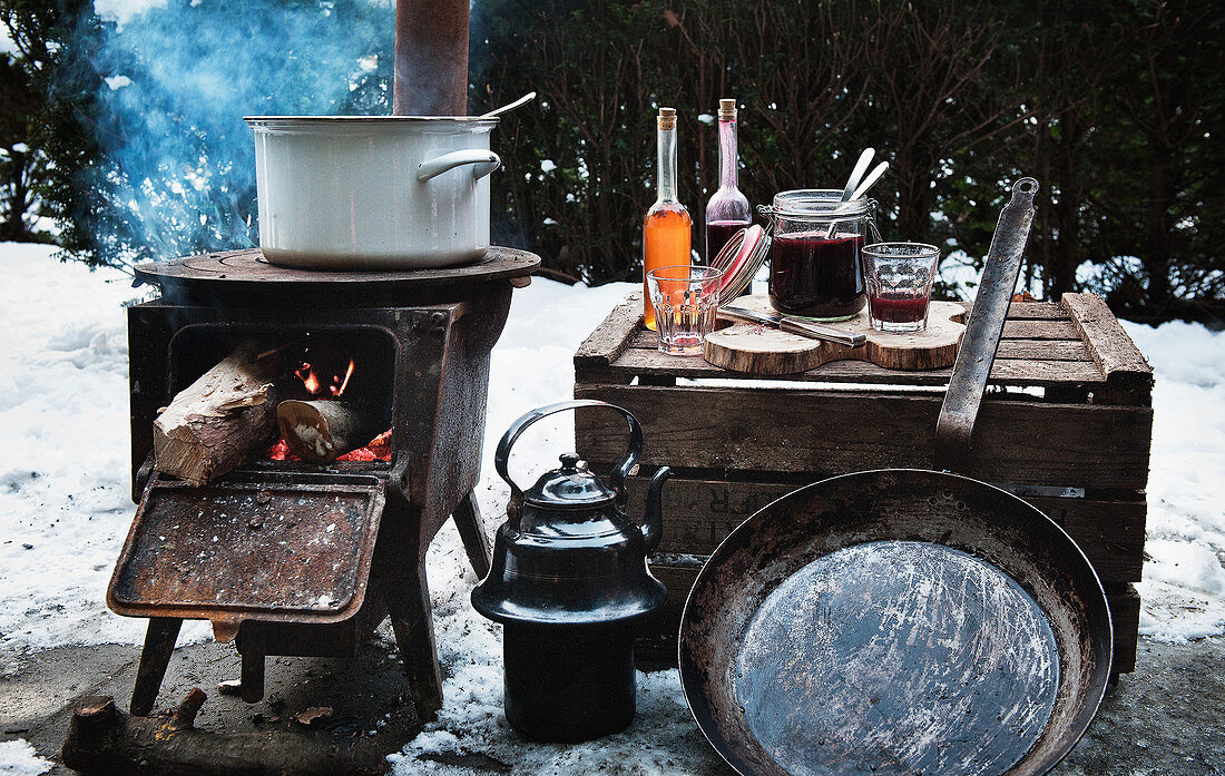 A winter barbecue with a rustic wood-fired oven and utensils in the snow