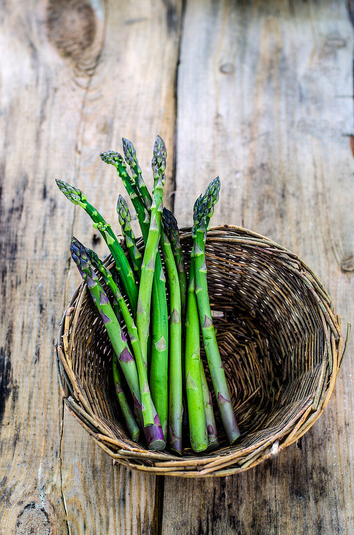 Fresh asparagus in a wicker basket on a wooden surface