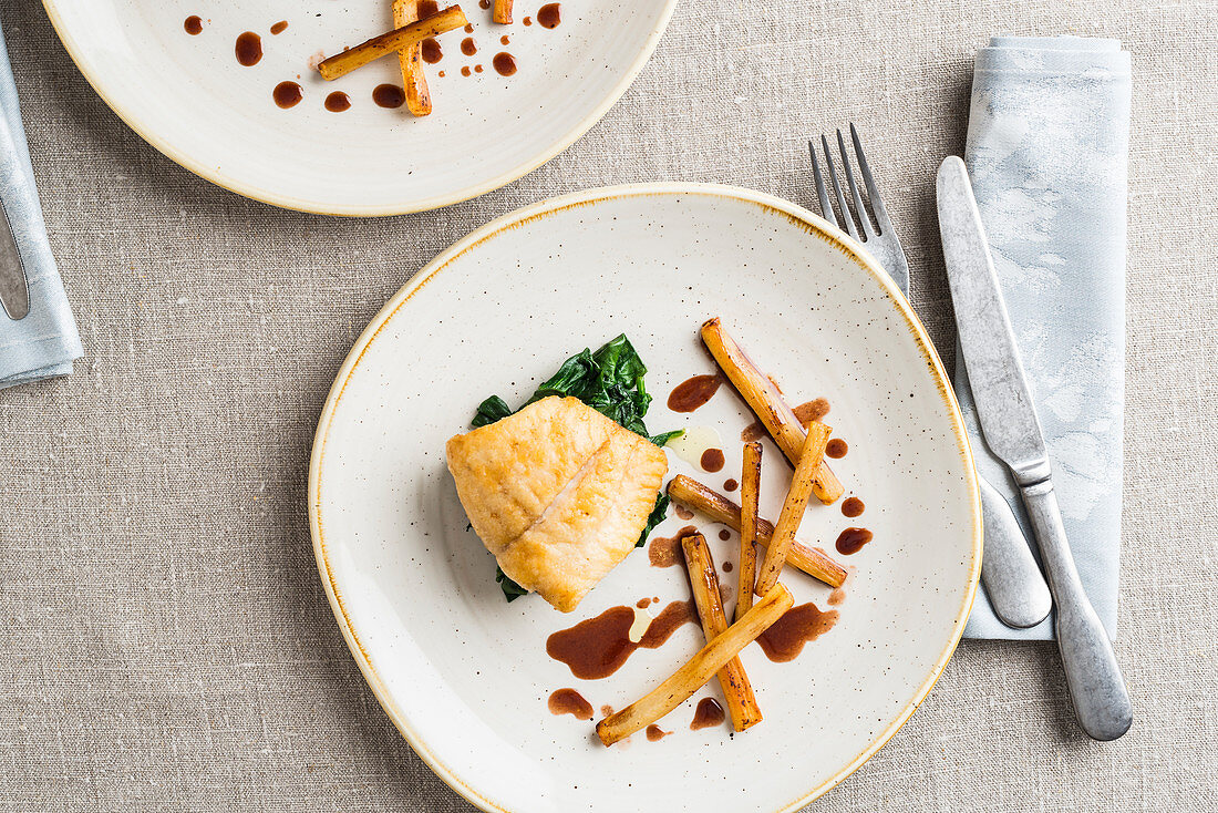 Fish fillet on a bed of spinach with fried black salsify